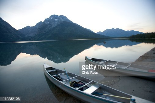 Two canoes at dusk are beached on the shore of Lake Leigh with the Grand Tetons in the distance.