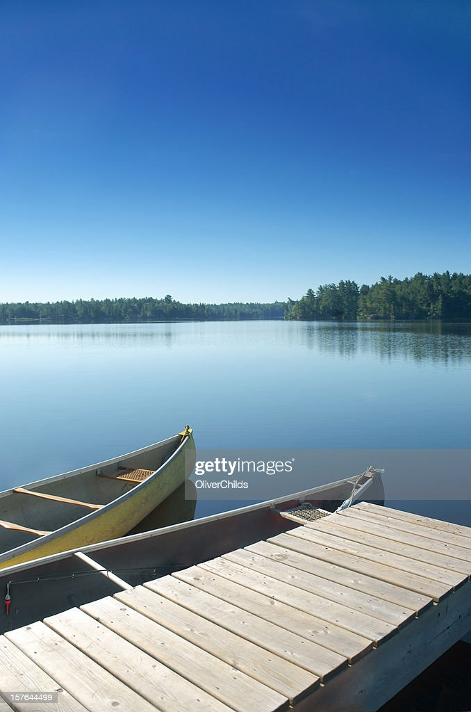 Two canoes docked on a still lake.