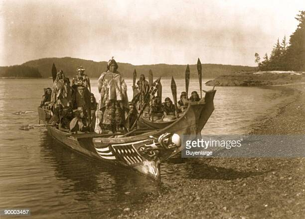 Two canoes pulled ashore with wedding party bride and groom standing on 'bride's seat' in the stern relative of the bride dances on platform in bow