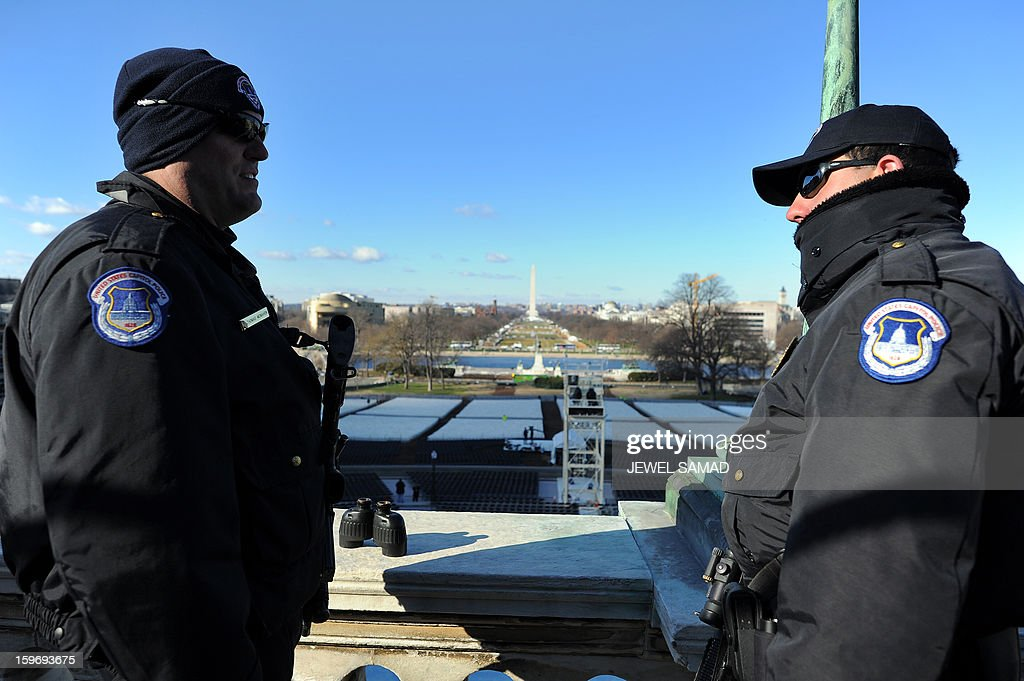 Two Capiol Policemen stand guard as preparations continue for the second inauguration of US President Barack Obama in Washington on January 18, 2013. Crowds may be smaller on the January 21 inauguration than when Barack Obama was first sworn into office in 2009, but security is as tight as ever, with experts warning a 'lone wolf' would pose the greatest threat. Between 500,000 and 800,000 people are expected to pass through the National Mall, the immense greenway that leads up to the Capitol, compared to the 1.8 million spectators who came to applaud Obama four years ago. AFP PHOTO/Jewel Samad