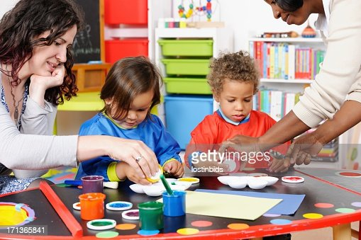 Two Carers/ Teachers Supervising Little Boys During Art And Craft