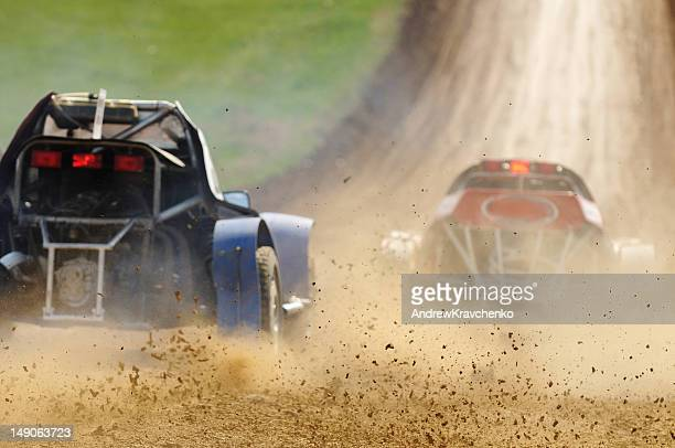 Two cars racing in a dirt road