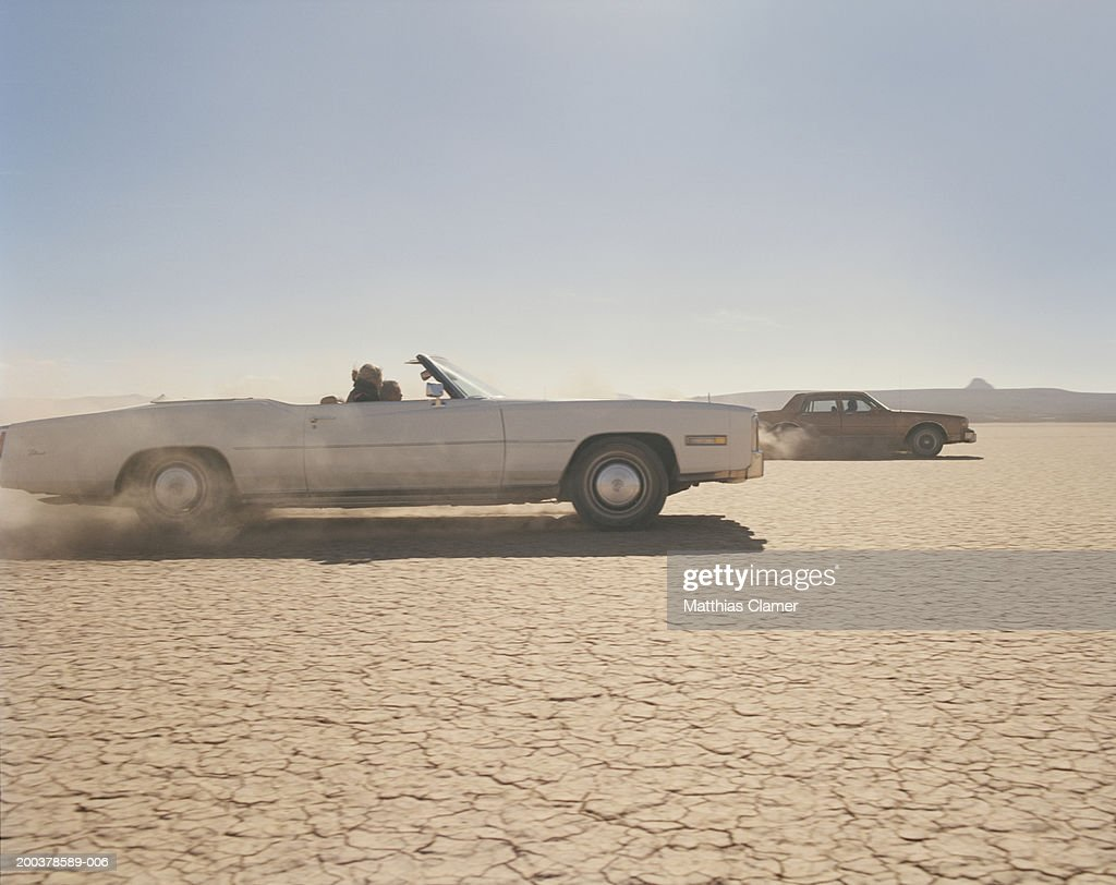 Two cars racing in desert, side view