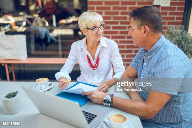 Two casual business people discussing business issues in cafe