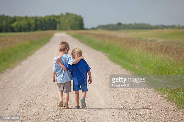 Due caucasico ragazzi camminare lungo una strada di campagna