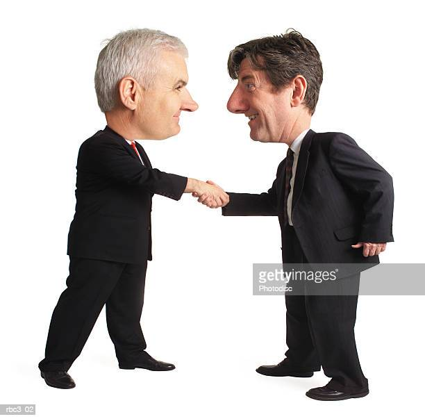 two caucasian business men in dark suits shake hands and smile