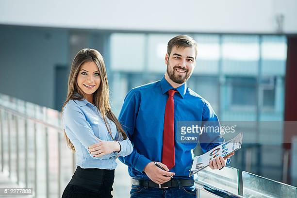 Two caucasian business people in modern office discussing business performances