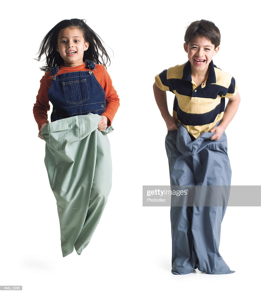 two caucasian children play together by jumping along in pillow case sacks