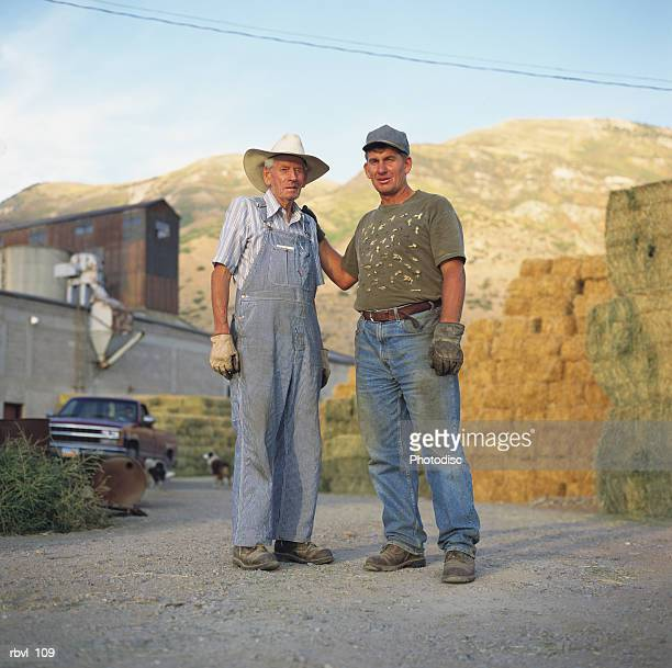 two caucasian farmers dressed for working in the field are standing together in front of bales of hay and a large barn