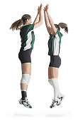 two caucasian female volleyball players from the same team jump in the air and high five each other celebrating a victory