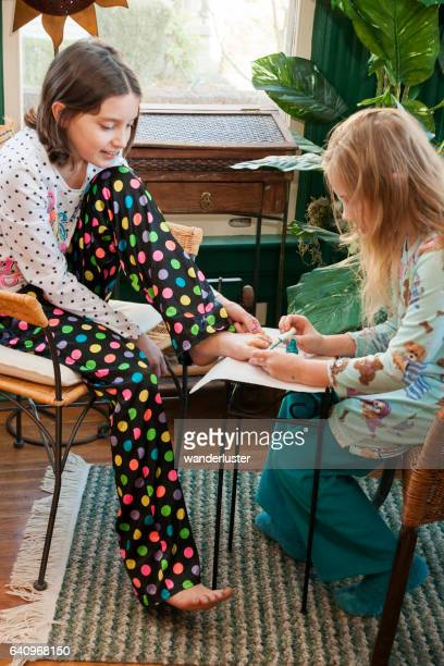 Two Caucasian girls aged 11 years paint each other's toenails wearing their pajamas, Indiana, USA