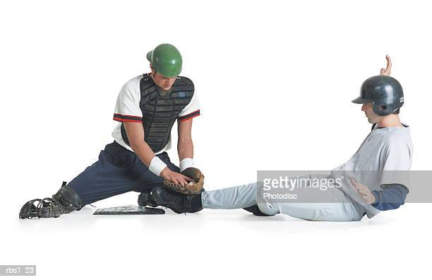 two caucasian men are dressed in baseball uniforms as one in a catcher vest tags the other wearing a batter helmet out