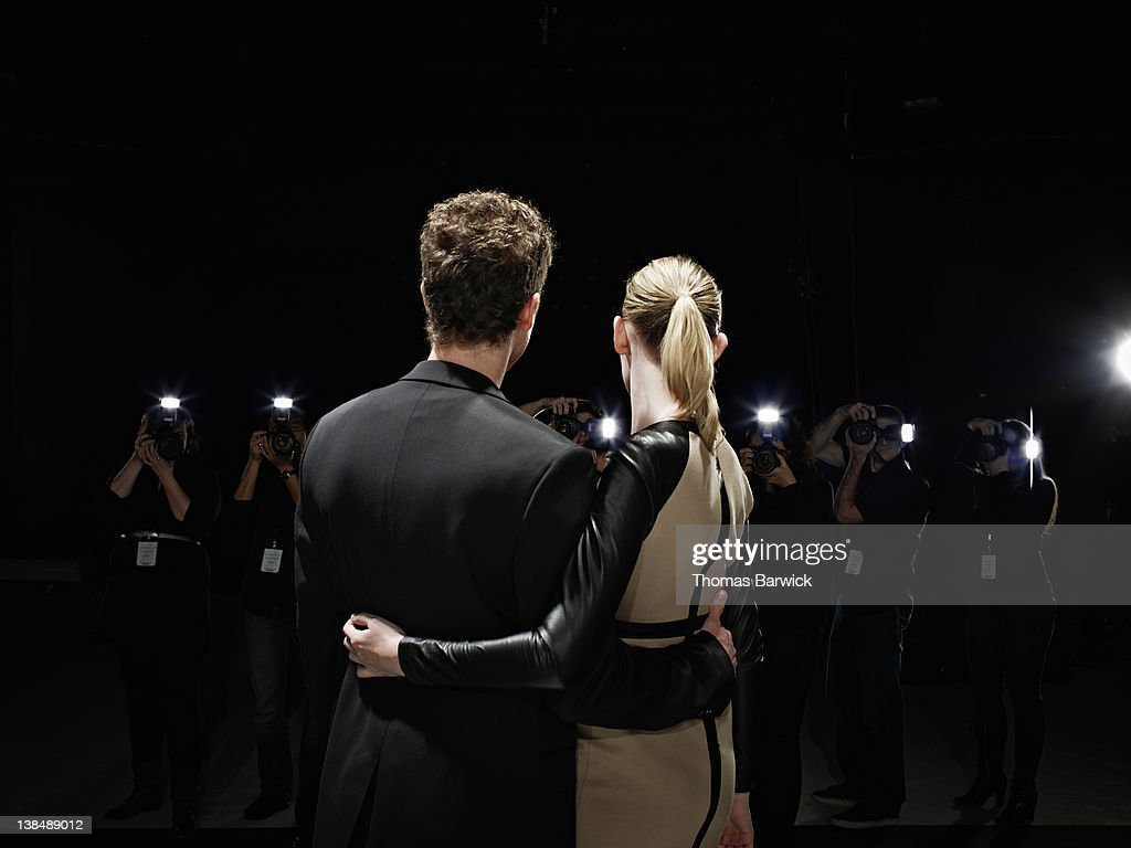 Two celebrities being photographed by paparazzi : Stock Photo