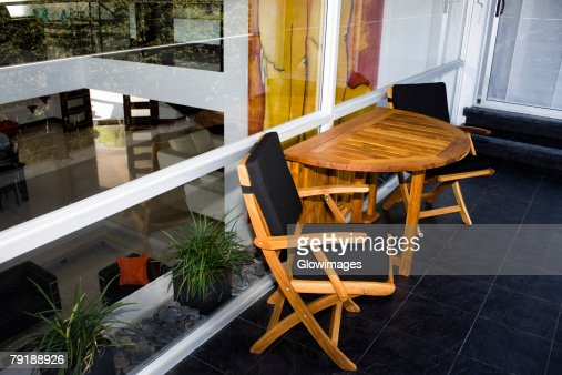 Two chairs and a table outside a house : Foto de stock