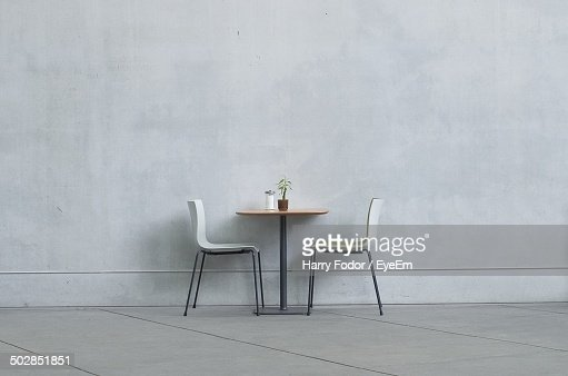 two chairs and table against the wall stock photo getty images. Black Bedroom Furniture Sets. Home Design Ideas