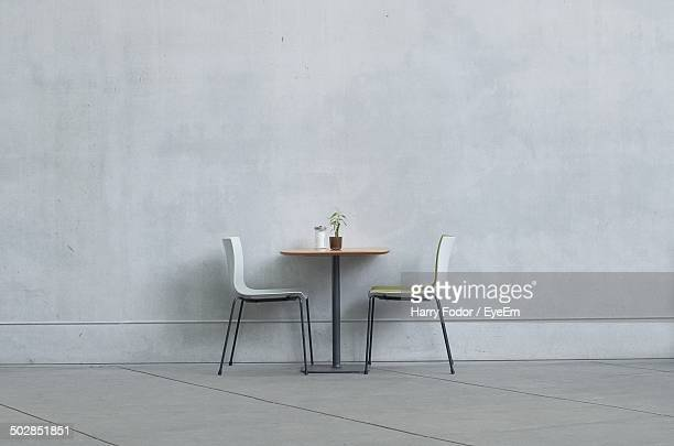 Two chairs and table against the wall