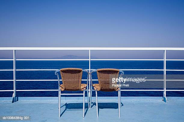 Two chairs on a ship deck, rear view