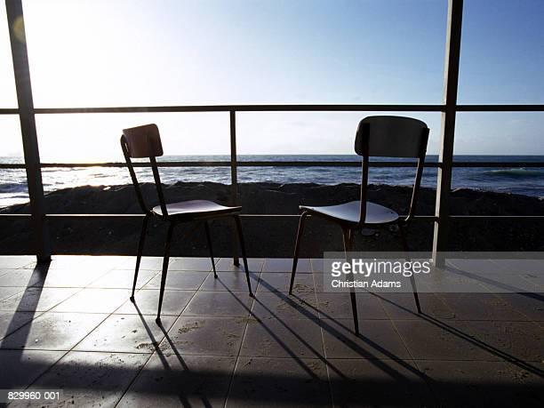 Two chairs on balcony overlooking sea