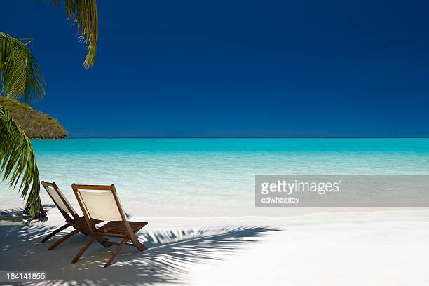Two chairs under palm trees on Virgin Island beach