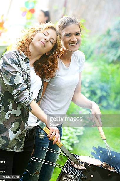 Two cheerful beautiful young women preparing party barbecue in garden