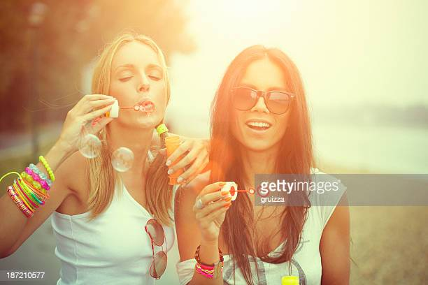Two cheerful friends having fun and blowing bubbles