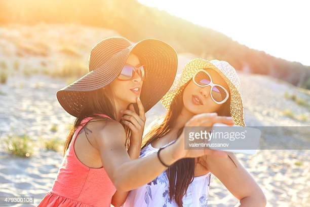 Two cheerful friends using  smart phone on the beach