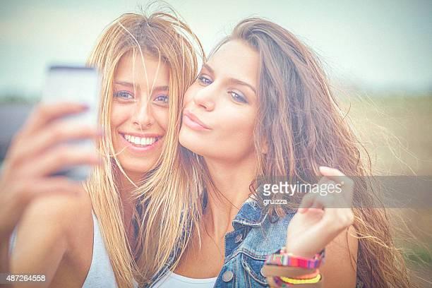 Zwei fröhlich hipster Freunde nehmen selfie Fotos auf Smartphone