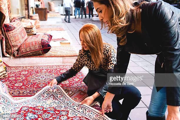 Zwei Fröhliche Frauen kaufen Teppiche