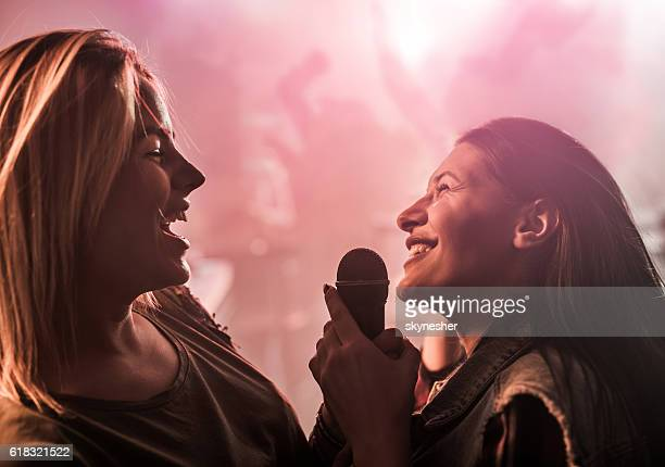 Two cheerful women singing karaoke at disco club.