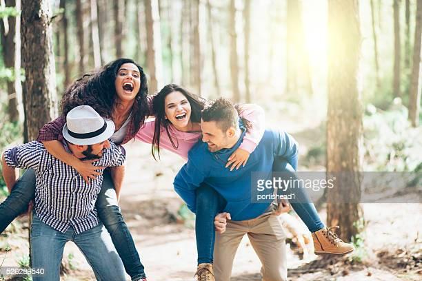 Deux jeunes couples agréable à porter sur le dos dans la belle forêt