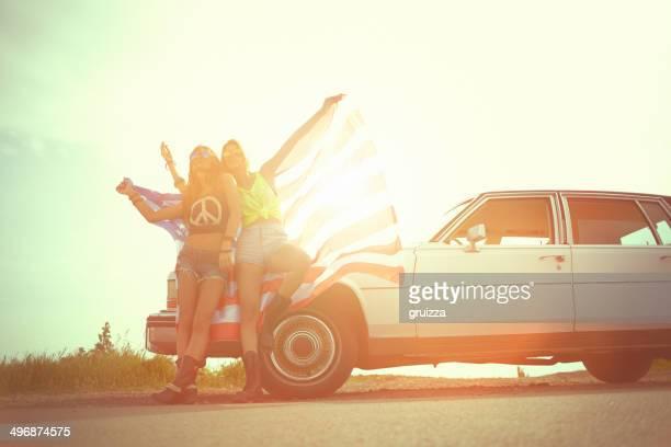 Duas mulheres alegres jovens hipster envolto na Bandeira dos Estados Unidos da América