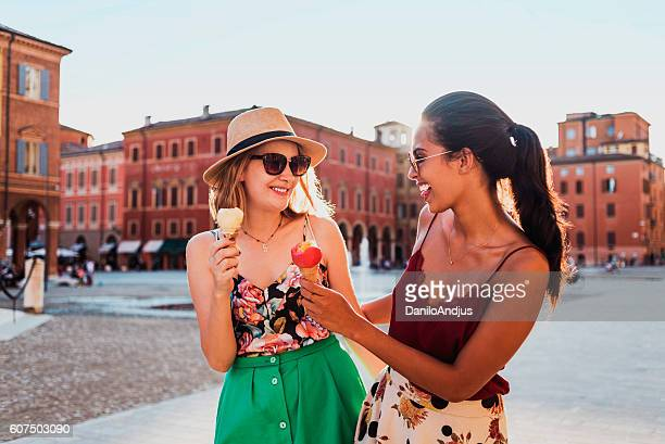two cheerful young women eating ice cream and having fun