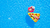 AERIAL TOP DOWN Relaxed girls in pink bikini swimsuits lying on fun inflatable pizza and flamingo floating loungers on water. Girlfriends on summer vacation enjoying colorful floaties in swimming pool