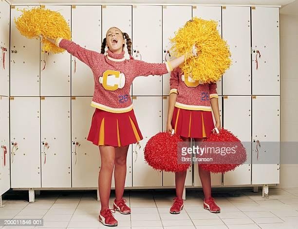 Two cheerleaders in locker room, one waving pom-poms