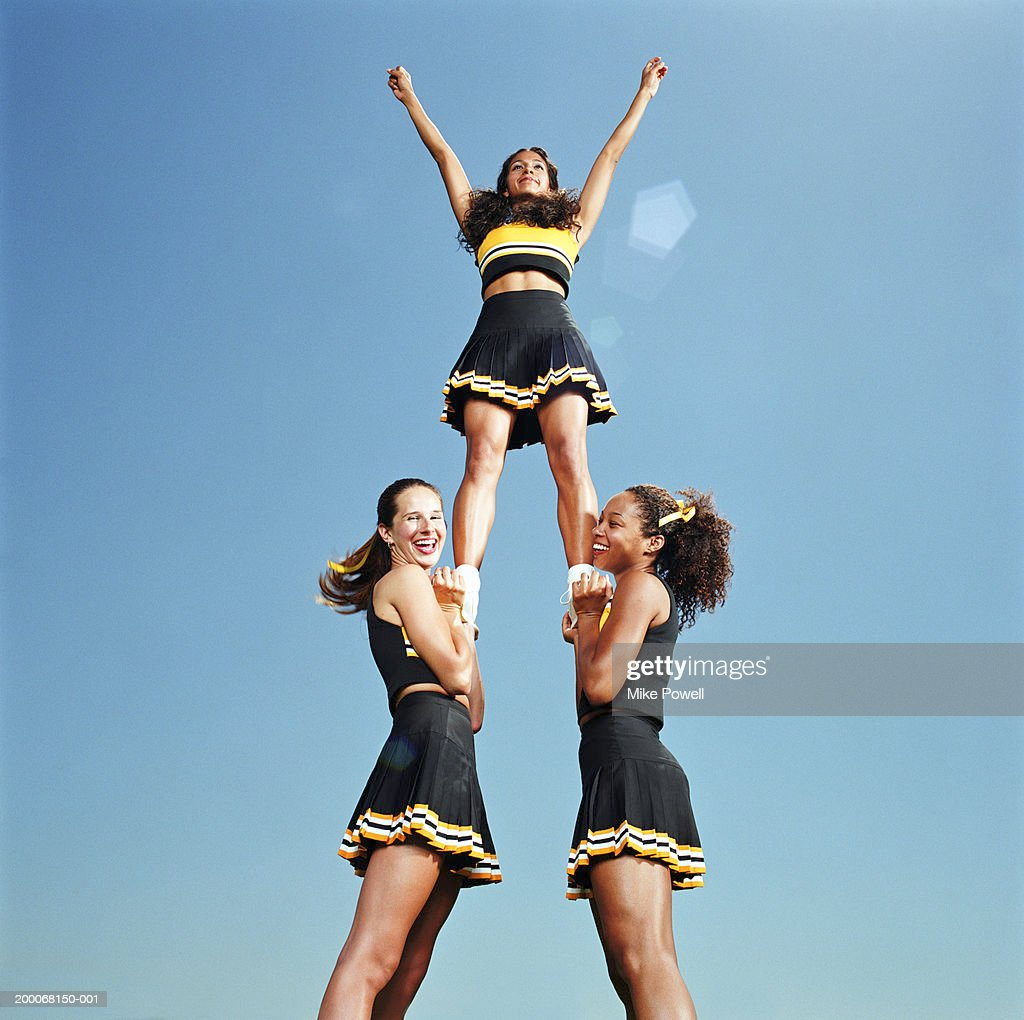 Two cheerleaders lifting squad member in air, portrait, low angle