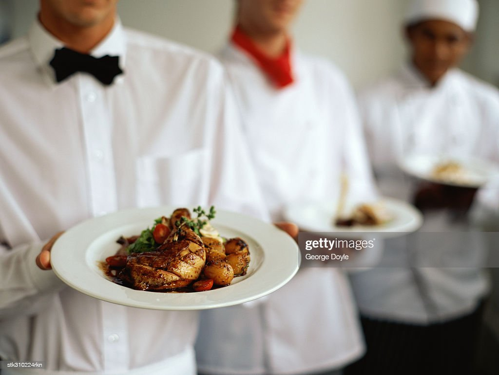 two chefs and a waiter standing in a row : Stock Photo