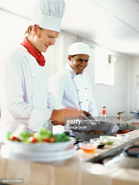 two chefs preparing food in the kitchen