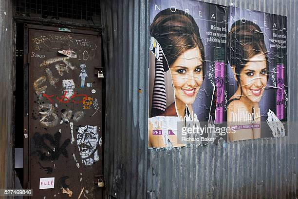 Two Cheryl Cole L'Oreal poster ads are seen next to a filthy derelict doorway with stencilled face a scene of wealth versus poverty The fashion...