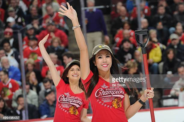 Two Chicago Blackhawks icecrew girls wave to the crowd in the first period of the NHL game between the Chicago Blackhawks and the Minnesota Wild at...
