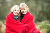 Two chidren wrapped in blanket outdoors