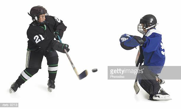 two child caucasian male hockey players from opposing teams confront each other when one shoots the puck as the goalie tries to block