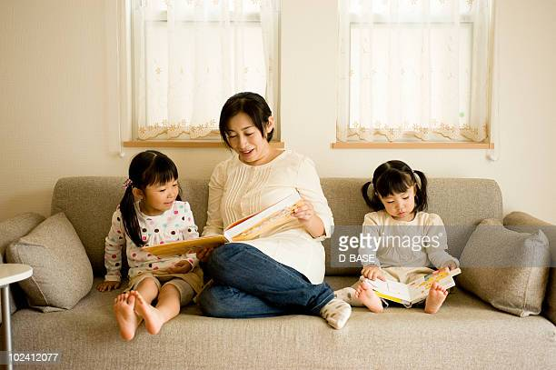 Two child reading book with her mother at home.