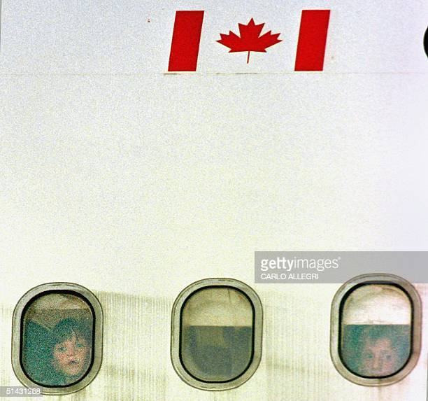 Two child refugees from Kosovo look out the window of an airplane from Macedonia at Trenton Air Force base in Canada 05 May 1999 Canadian immigration...