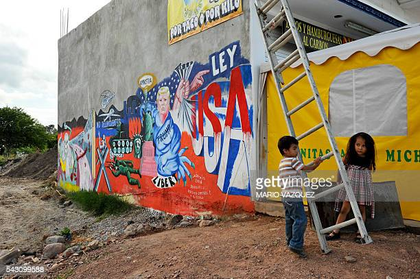 Two children are seen next to the mural paint made by Mexican artist Luis Sotelo called 'We are migrants not criminals' in Tonatico Mexico on 25 June...