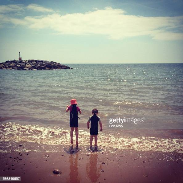 Two children at sea edge on beach at Sidmouth in summer