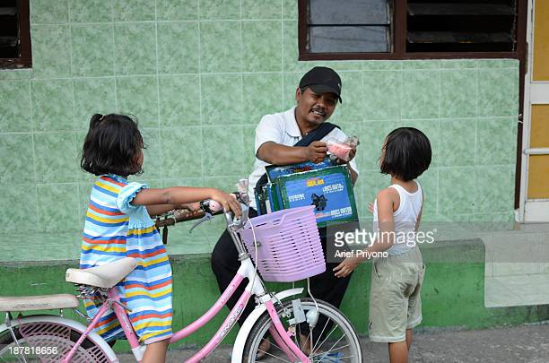 Two children buy Arum Manis Suwito is a traveling salesman who sells Arum Manis or commonly called Cotton Candy He is selling since 1985 Uniquely to...