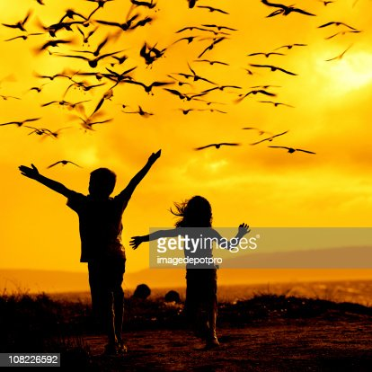Two Children Chasing Seagulls : Stock Photo