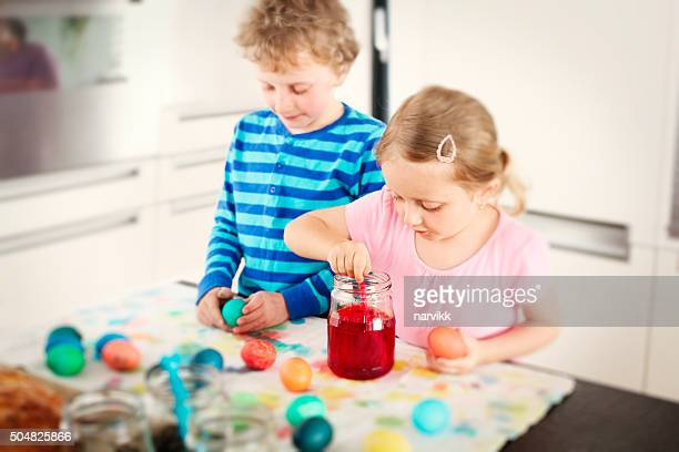 Two children coloring together easter eggs