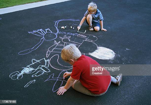 Two children drawing chalk pictures of dinosaurs