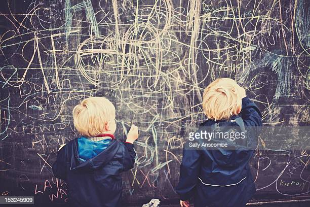 Two children drawing on board